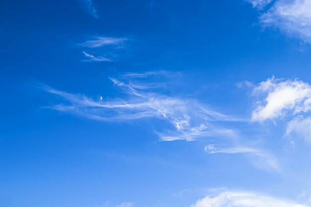 Soft clouds and the moon met in a bright blue sky. natural beauty