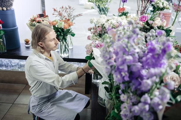 부드러운 색상. 꽃집에서 일하는 동안 앞치마를 입고 집중된 남성 사람