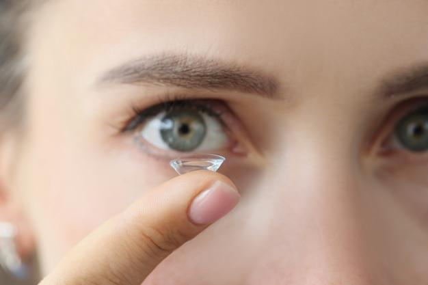 매일 렌즈에 맞는 여성 눈의 배경에 대해 여성 손가락에 소프트 콘택트 렌즈