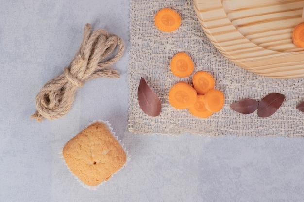大理石の背景に柔らかいクッキー、ロープ、ニンジンのスライス。高品質の写真