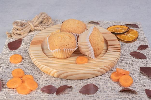 Мягкое печенье, кусочки веревки и моркови на мраморном столе. фото высокого качества
