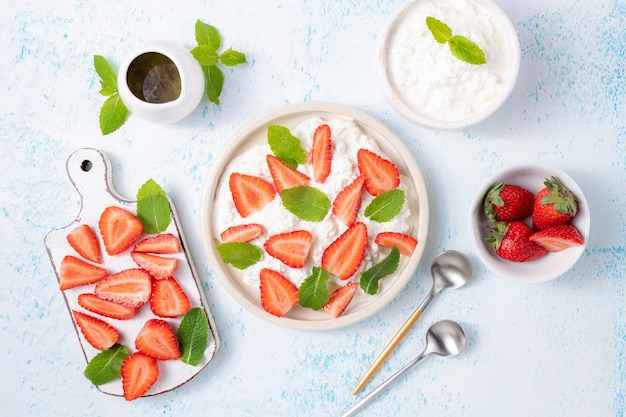 Soft cream cheese or organic curd with fresh strawberries and mint leaves top view on light blue background
