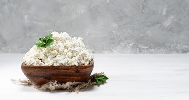 부드러운 두부 자연 건강 식품, 건강에 좋은 다이어트 식품. 흰색 나무 배경에 민트 잎이 있는 전통적인 나무 그릇에 있는 코티지 치즈. 클로즈업, 복사 공간이 있는 선택적 초점.