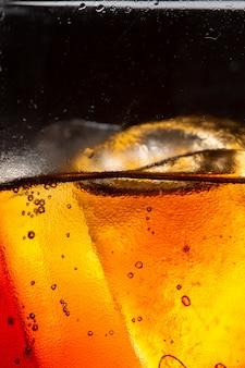 お祝いパーティーのコンセプトで暗い背景のコーラガラスに氷のスプラッシュとソフトドリンクグラス