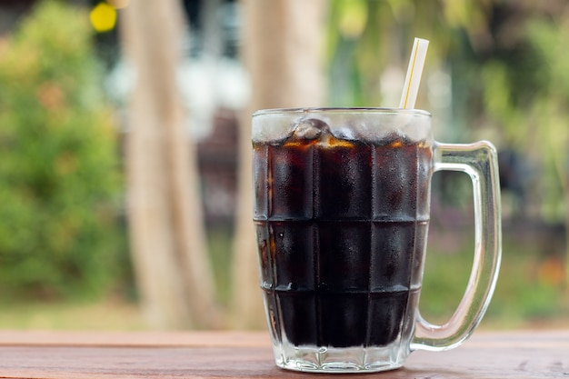 Soft drink iced cola in a glass side view on wooden desk with green natural out door background during day time in summer