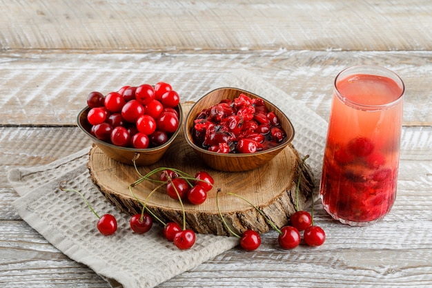 Soft drink with cherries, wooden board, jam in a jug on wooden and kitchen towel high.