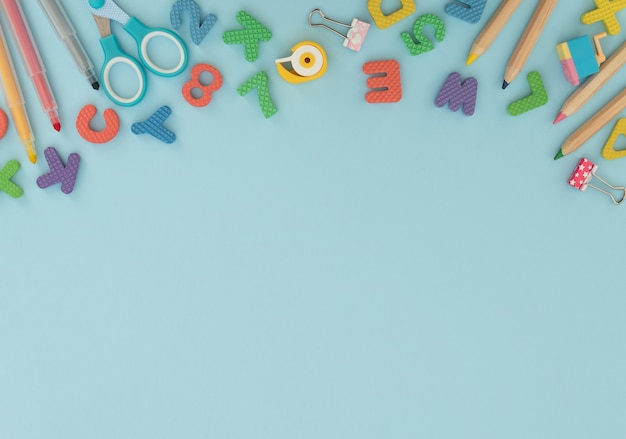 Soft english letters and numbers with school and office supplies on blue.