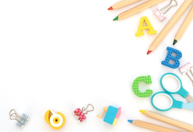 Soft english letters with school and office supplies on white.