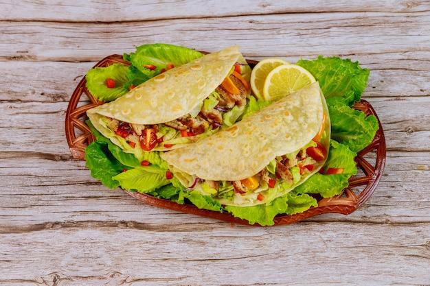 Мягкие мучные лепешки, фаршированные листьями салата, мясом и сыром на деревянной поверхности