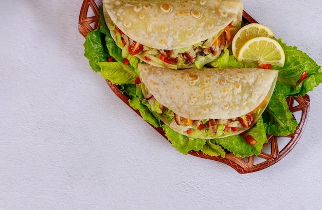 Мягкие мучные лепешки, фаршированные листьями салата, мяса и овощей на белом фоне.