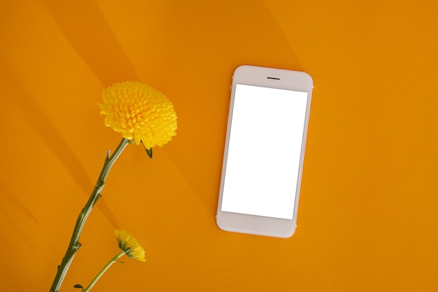 黄色いマリーゴールドの柔らかい花と濃い黄色の背景のコピースパに白い画面の携帯電話...