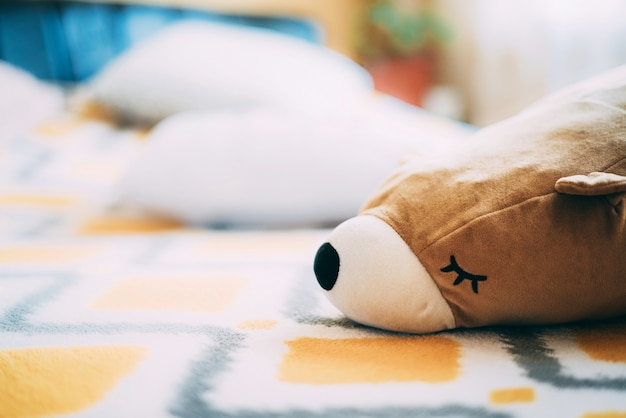 A soft fluffy bear toy lies on a nice yellow bedspread on the bed. sunny day. lazy mood. sleepy state at home. standby mode. toys for children and adults. spring at home because of virus. close up