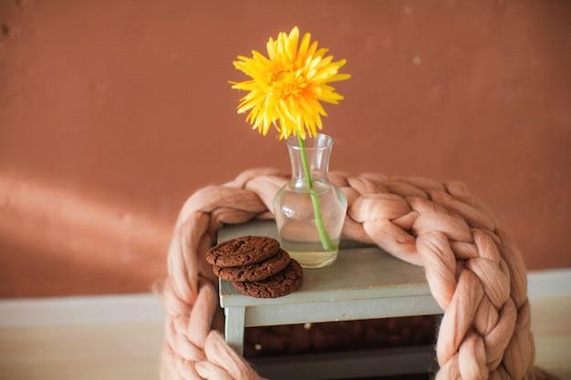 Мягкий пушистый плед в интерьере с цветами стула и чашкой кофе