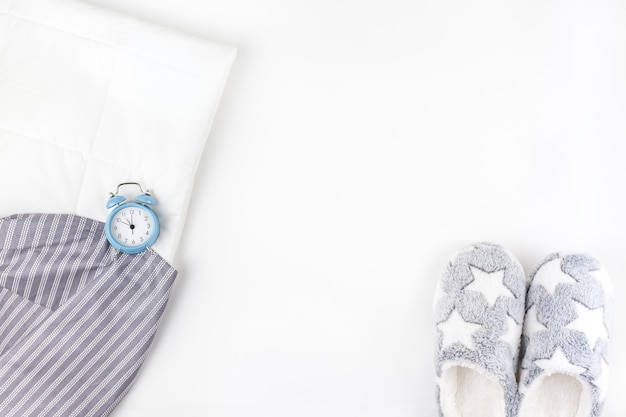 Soft fluffy slippers and blue alarm clock
