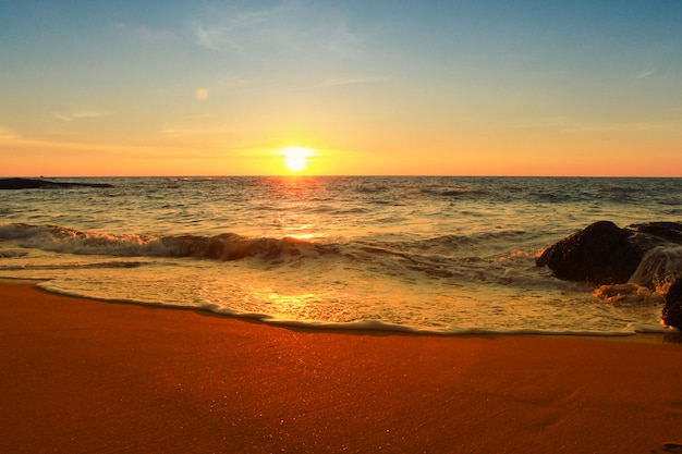 Soft foam sea waves beach in a golden sunset time on south pacific ocean with colourful reflections and sky backgound