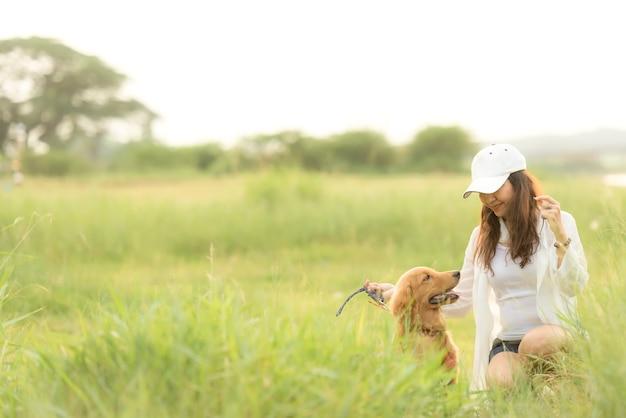 Мягкий фокус. азиатская женщина образа жизни играя с дружбой золотистого ретривера собаки счастливой и расслабляет напольный парк луга поля лета.