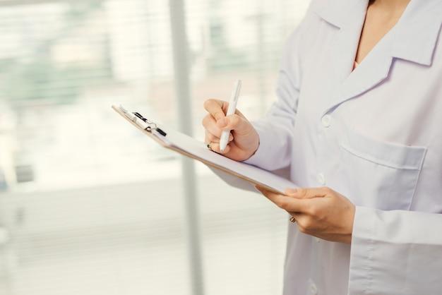 소프트 포커스 아시아 여성 의사 또는 간호사 환자 의료 차트를 들고.