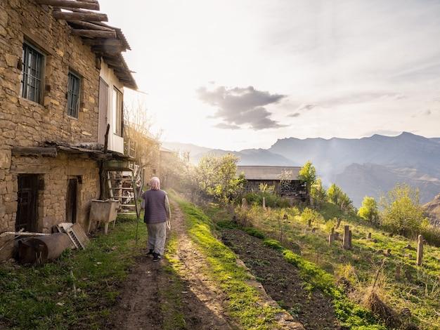 ソフトフォーカス。本物の田舎の女性が山の村を歩きます。後ろからの眺め。ダゲスタン。カヒブ。
