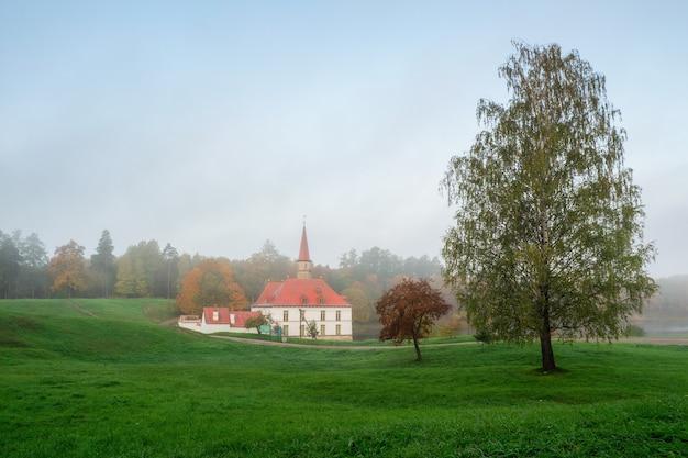 ソフトフォーカス。秋の朝の風景。黄金の木々と古い宮殿のある明るい秋の霧の風景。ガッチナ。ロシア。
