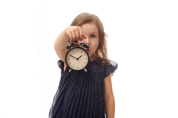 Soft focus on a black alarm clock in the hand of a pretty beautiful surprised baby girl in evening dress, posing against white background with copy space. black friday concept