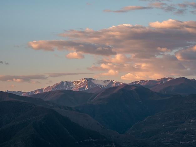 ソフトフォーカス。夜明けのコーカサス山脈。ピンクの夜明けの空を背景に山のシルエットと雰囲気のある風景。夕日や日の出のカラフルな自然の風景。色あせた色調の日没。