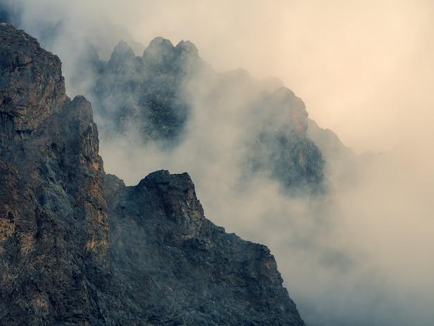 Мягкий фокус. опасное ущелье. драматический туман среди гигантских скалистых гор. призрачный атмосферный вид на большую скалу в облачном небе. низкие облака и красивые скалы. минималистичный пейзаж загадочного места.