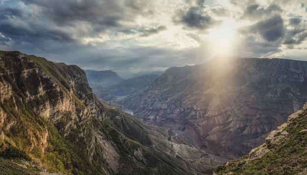 ソフトフォーカス。曇り空の下の雑多な岩の間の谷の川と劇的な山の風景。どんよりした空の下の深い峡谷に山の川がある風光明媚な白人の緑の風景。ダゲスタン