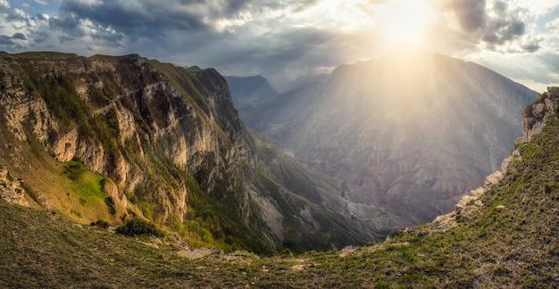 ソフトフォーカス。山の上の雲の切れ間から明るい太陽の光が差し込む劇的な風景。どんよりした空の下の深い峡谷に山の川がある風光明媚な白人の緑の風景。ダゲスタン