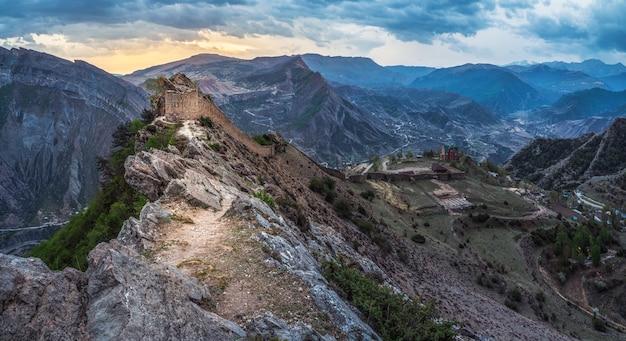 ソフトフォーカス。山の頂上にある古代の要塞での劇的な日の出。グニブ要塞はダゲスタンの歴史的記念碑です。ロシア。全景。