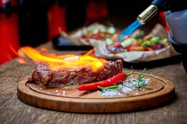 Мягкий фокус. антрекот из говядины мясо стейка на гриле с огнем на деревянной разделочной доске с веткой розмарина, перцем и солью. шеф-повар готовит вкуснейший шашлык на гриле. растопить масло
