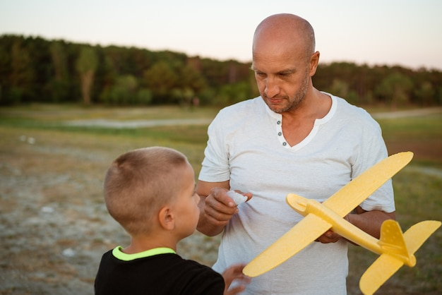 Soft focus of father and son playing toy airplane in meadow at sunset