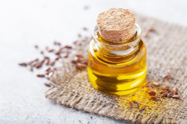 ソフトフォーカスの亜麻仁油を小瓶に入れ、健康的な食事のための種子 Premium写真