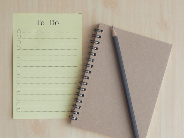 Soft focus to-do list paper with check box with black pencil on a light brown notebook