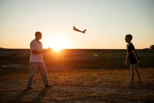 幸せな感情で日没時に牧草地でおもちゃの飛行機を遊ぶ父と息子のソフトフォーカス