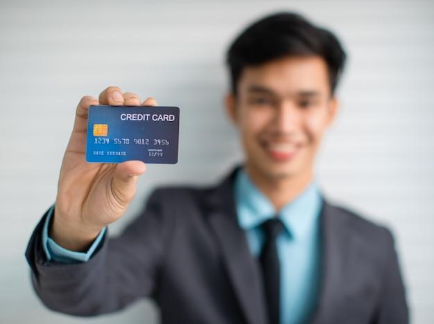 銀行サービスを宣伝しながらクレジットカードを示す男性起業家のソフトフォーカス