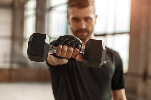 체육관에서 피트니스 운동을하는 동안 카메라에 무거운 아령을 보여주는 스포츠맨의 소프트 포커스