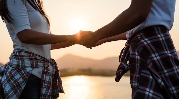 日没時に山の前で手をつないでいる2人のパートナーのソフトフォーカス