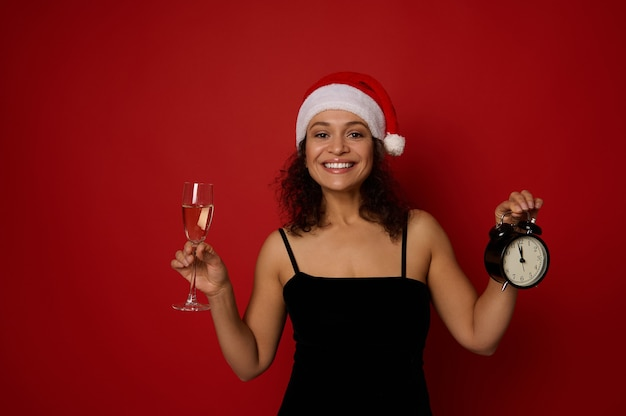 아름다운 이빨 미소로 웃는 산타 모자에 예쁜 여자의 손에 스파클링 와인과 알람 시계와 샴페인 플루트에 부드러운 초점. 복사 공간이 빨간색 배경에 크리스마스 개념