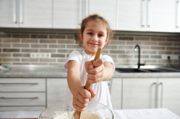 木のスプーンを持って生地をこねるぼやけた美しい笑顔の女の子の手にソフトフォーカス。料理をしている子供たち