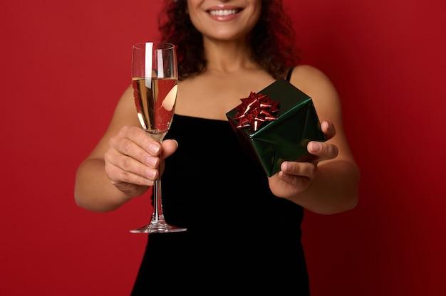 아름다운 이빨 미소를 가진 예쁜 여성의 손에 반짝이는 선물 종이로 포장된 상자와 스파클링 와인을 곁들인 샴페인 플루트에 부드럽게 초점을 맞춥니다. 복사 공간이 빨간색 배경에 크리스마스 개념