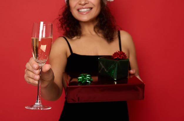반짝이는 빨간색 녹색 선물 종이에 싸인 크리스마스 선물 상자를 들고 아름다운 이빨 미소를 지닌 흐릿한 쾌활한 웃는 여성의 배경에 스파클링 와인과 함께 샴페인 플루트에 부드러운 초점