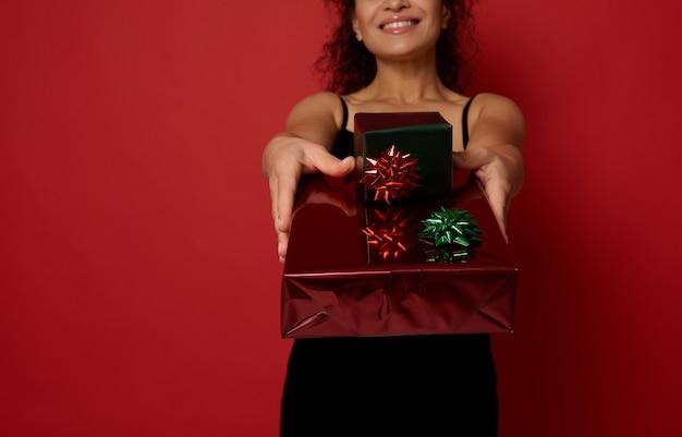 빨간 배경 위에 격리된 카메라에 보여주는 아름다운 이빨 미소를 가진 흐릿한 예쁜 여성의 뻗은 손에 있는 크리스마스 선물에 부드러운 초점. 광고 복사 공간이 있는 새해 개념