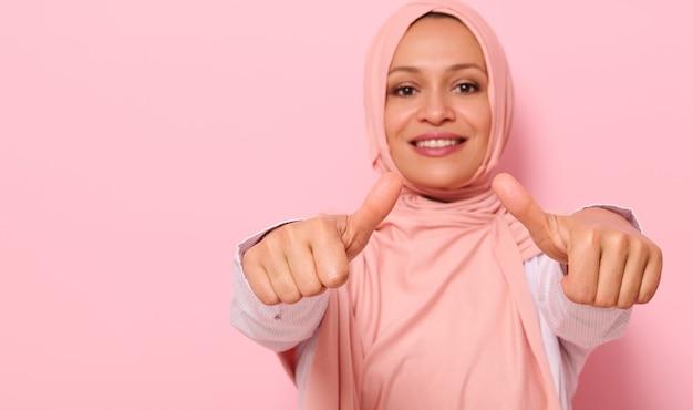 ピンクのヒジャーブで歯を見せる笑顔のアラブのイスラム教徒の女性とぼやけた笑顔の手にソフトフォーカス、カメラに向かって親指を示し、テキスト用のスペースで色付きの背景の上に分離