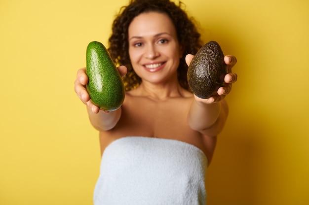 Мягкий фокус на спелых готовых к употреблению фруктах авокадо в руках размытой полуобнаженной кудрявой женщины, завернутой в полотенце на желтом фоне
