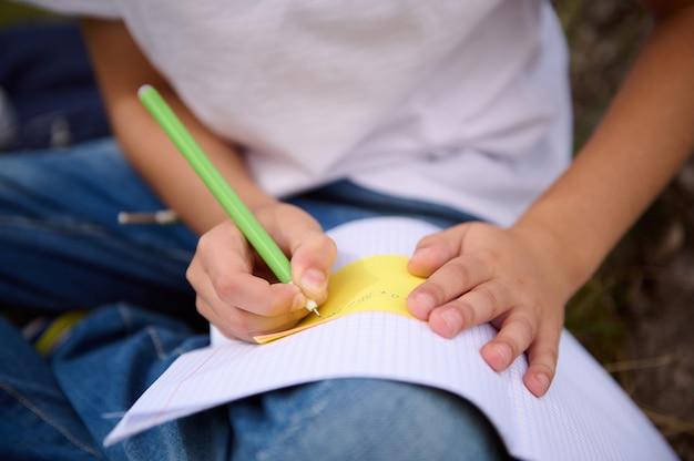 ペンを持って宿題をする、コピーブックに書く、数学の課題を解決する男子生徒の手にソフトフォーカス。学校に戻る、知識、科学、教育、概念の学習。閉じる。