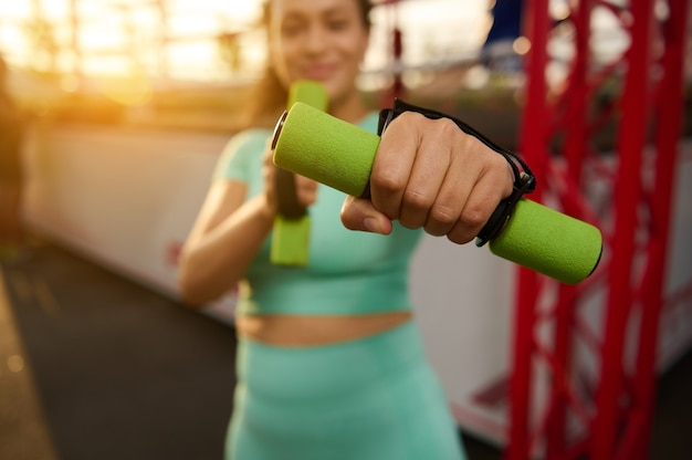 작은 아령을 들고 권투 경기장의 배경에 서 있는 스포티한 여성의 뻗은 손에 부드러운 초점. 흐릿한 피트니스 여성은 일출 시 야외에서 운동합니다.