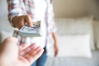 Soft focus on woman hands proposing money us dollar bills to you