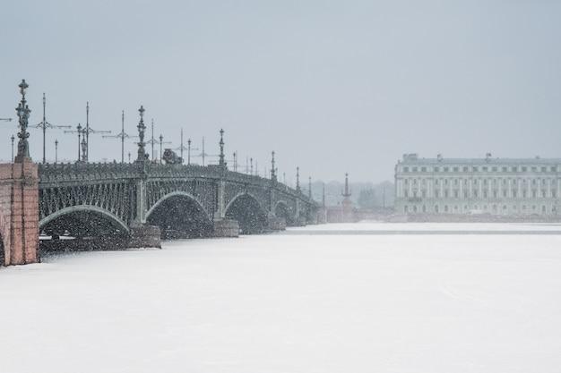 Мягкий фокус. дворцовый мост в санкт-петербурге во время снегопада зимой. минималистичный зимний городской вид.