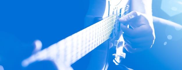 소프트 포커스 사진입니다. 그림자에서 일렉트릭 기타를 연주하는 남자. 악기 사진입니다. 스포트라이트를 받는 뮤지션. 밝은 그림자가 있는 창의적인 스타일.