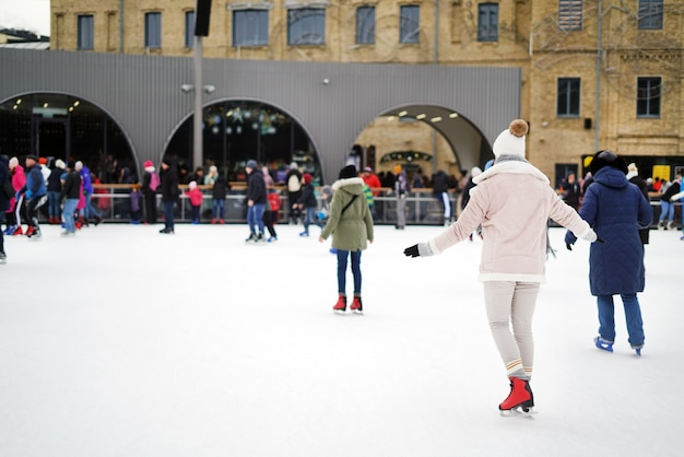 Soft focus photo of people skating on an ice rink wearing hats and scarves